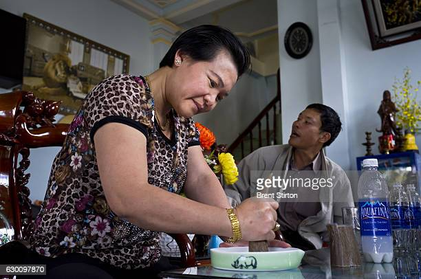 A wealthy Vietnamese woman sits and grinds Rhino horn for her personal consumption in a roadside cafe in Baoloc Vietnam on October 6 2011 The dealer...