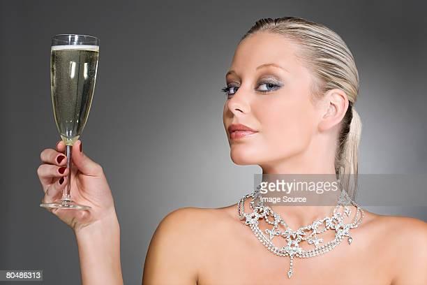 富裕層を持つ女性のグラスシャンパン