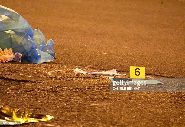 A weapon used in the shootout of suspected Berlin truck attacker Anis Amri in Milan is marked as evidence as it lays on the ground on December 23...