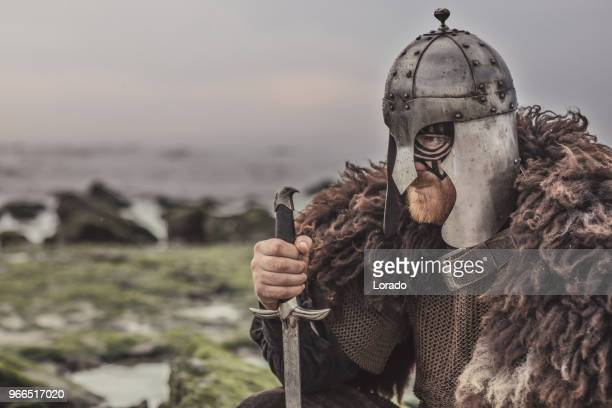 Weapon wielding bloody medieval warrior alone on a cold seashore