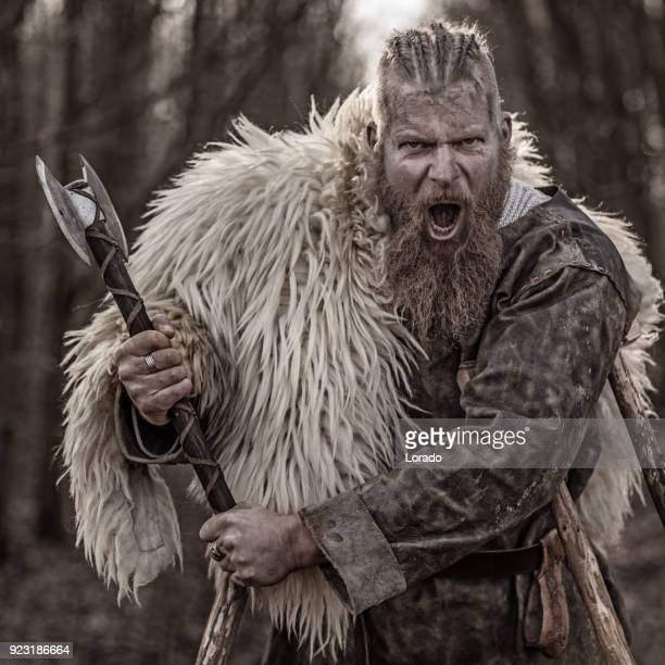 weapon wielding bloody viking warrior alone in a winter forest - barbarian stock photos and pictures
