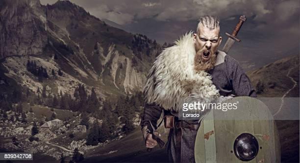 Vapen svingar blodiga viking krigare i känslomässiga pose mot bergskedjan