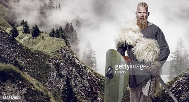 Weapon wielding bloody viking warrior in emotional pose against mountain range