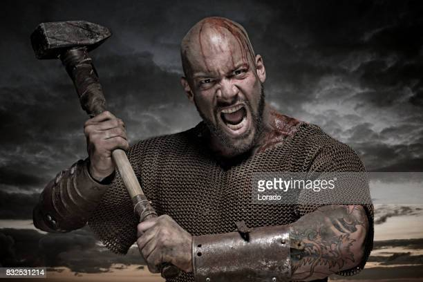 weapon wielding bloody viking warrior in emotional pose - viking stock photos and pictures