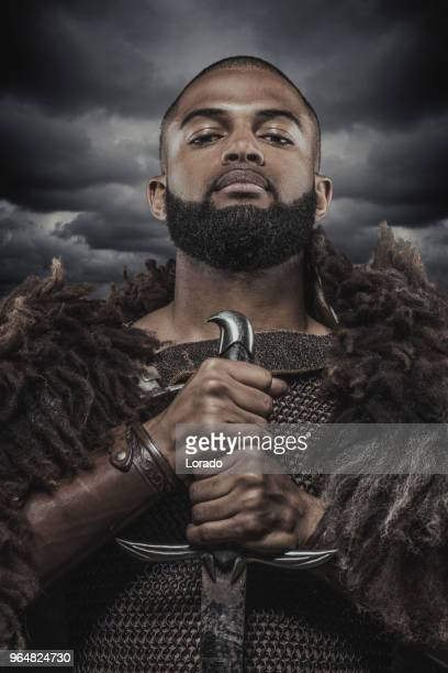 weapon wielding viking inspired black warrior alone in front of a cloudy sky - film poster stock pictures, royalty-free photos & images