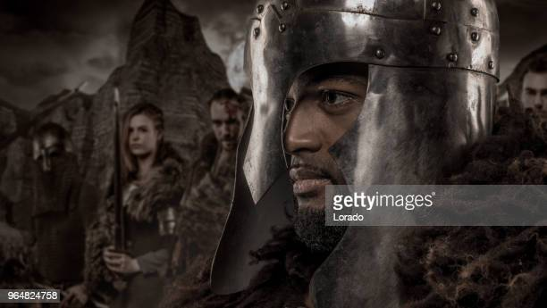 weapon wielding viking inspired black warrior alone in front of a mountain range and clan - movie poster stock photos and pictures