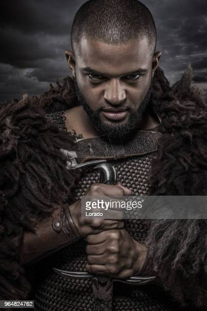 weapon wielding viking inspired black warrior alone in front of a cloudy sky - movie poster stock photos and pictures