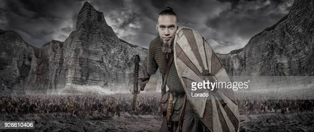weapon wielding viking warrior alone in front of viking hoard and mountain range - barbarian stock photos and pictures