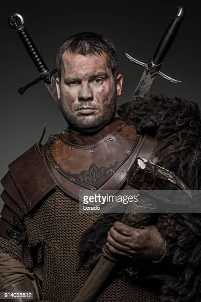 Weapon wielding viking warrior brunette male in studio shot