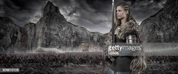 Weapon wielding viking warrior female alone in front of viking hoard and mountain range