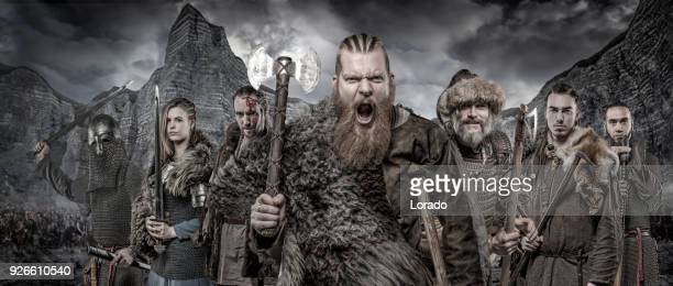 Weapon wielding viking warriors in formation in front of viking hoard and mountain range