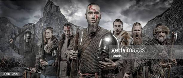 weapon wielding viking warriors in formation in front of viking hoard and mountain range - movie poster stock photos and pictures