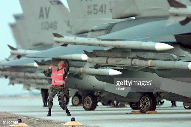 Weapons Crew Chief, Checks The Positioning Of Missiles On A Us F-16 As He Prepares To Launch It As Part Of The Nato Airstrike Operation Determined...