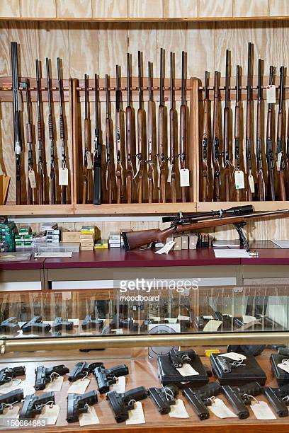 weapons displayed in gun shop - gun shop stock photos and pictures