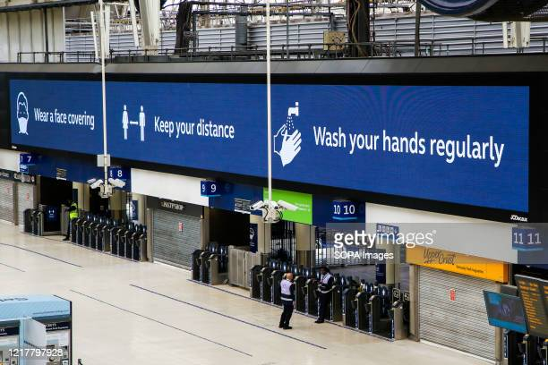 Wear a face covering. Keep your distance. Wash your hands regularly is displayed on a Coronavirus public information campaign poster at London...