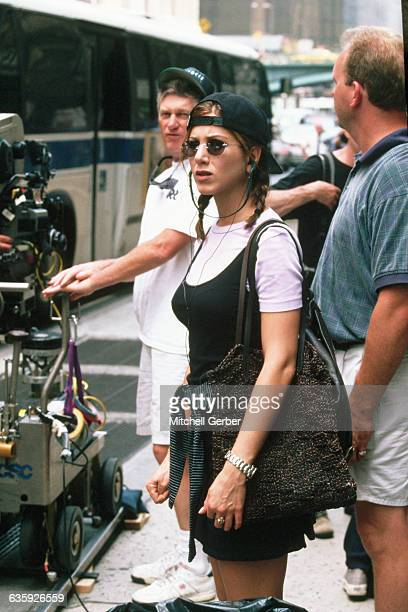 Wearing a backwards baseball cap and sunglasses actress Jennifer Aniston stands on the set of the motion picture Picture Perfect during filming on...