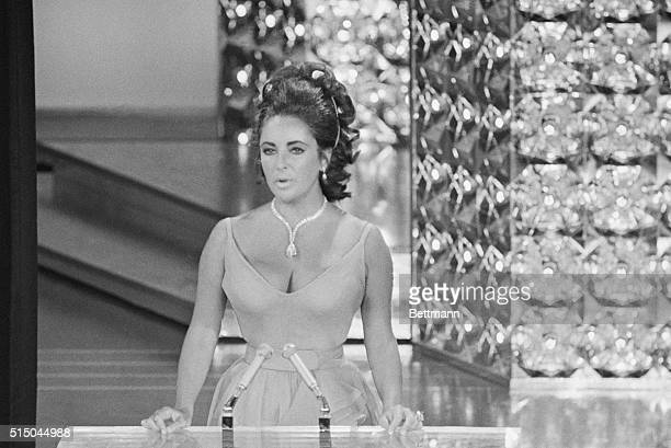 """Wearing a beautifully displayed million dollar diamond and low-cut gown, actress Elizabeth Taylor presents the """"Oscar"""" for the best movie to the..."""
