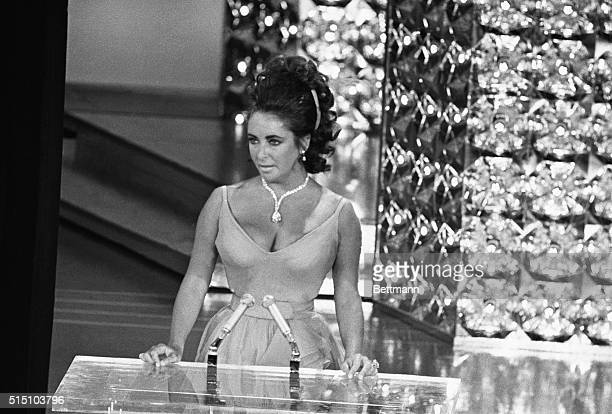 Wearing a beautifully displayed million dollar diamond and lowcut gown actress Elizabeth Taylor presents an Oscar for the best movie in the 42nd...