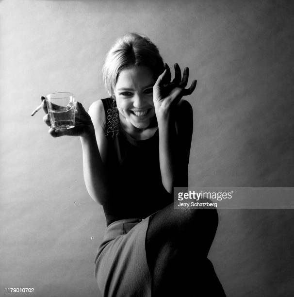 Wearing a black tank top gray miniskirt and black stockings American model and actress Edie Sedgwick a glass and cigarette in one hand laughs as she...
