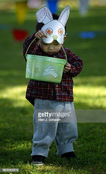 Wearing a bunny mask he made himself Michael Chang 21 months–old views his winnings from an Easter egg hunt Saturday April 19 at Modjeska Park in...