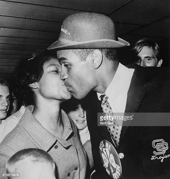 Wearing a button reading Kiss Me I'm Irish University of Southern California football hero OJ Simpson gets a welcome home kiss from his wife...