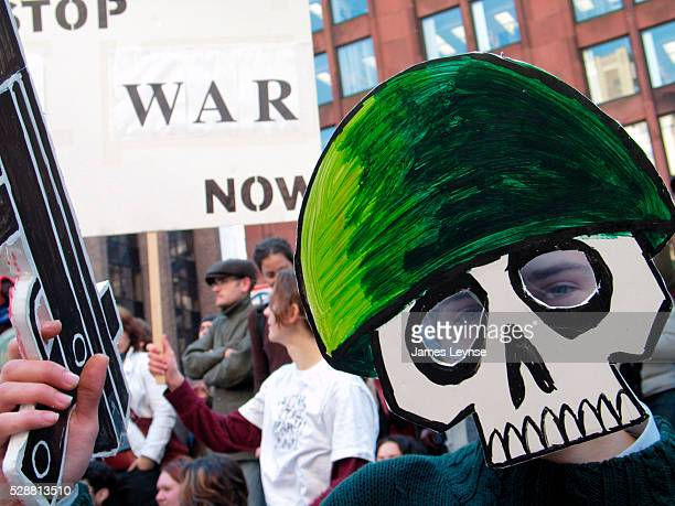 Wearing a cartoon death mask and helmet while wielding a paper gun a student at New York University protests a possible US war against Iraq Several...