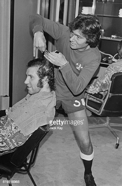 Wearing a Chelsea strip British hairdresser Vidal Sassoon styles the hair of Chelsea footballer Peter Osgood 2nd March 1972 Sassoon is cutting the...