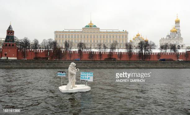 Wearing a costume of polar bear a Greenpeace activist takes part in a staged show on the Moskva River in front of the Kremlin in Moscow on April 1...