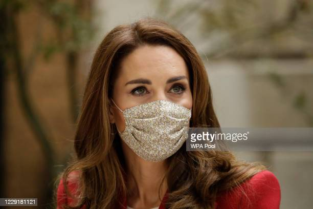 Wearing a face covering to curb the spread of coronavirus Catherine Duchess of Cambridge meets pharmacist Joyce Duah as she and Prince William visit...