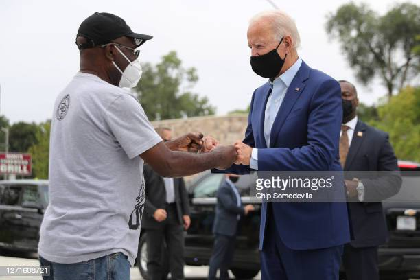 Wearing a face mask to reduce the risk posed by the coronavirus, Democratic presidential nominee Joe Biden gives a fist bump to Clement Brown while...