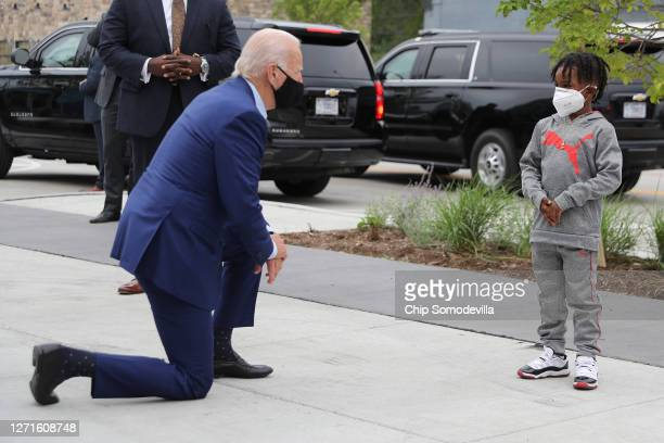 Wearing a face mask to reduce the risk posed by the coronavirus, Democratic presidential nominee Joe Biden kneels to chat with C.J. Brown while...