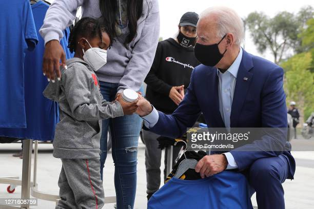 Wearing a face mask to reduce the risk posed by the coronavirus, Democratic presidential nominee Joe Biden shops at Three Thirteen, an apparel store...