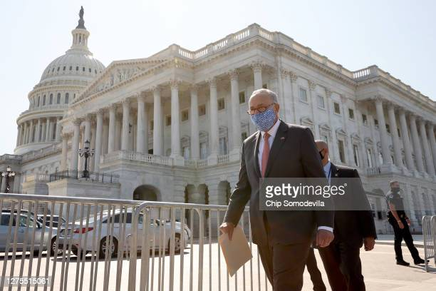 Wearing a face mask to reduce the risk posed by the coronavirus, Senate Minority Leader Charles Schumer walks out of the U.S. Capitol and heads for a...