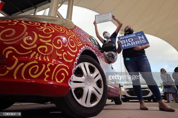 Wearing a face masks to reduce the risk posed by the coronavirus, Sophia Hildalgo and Amore Rodriguez of Miami stay with their car decorated in...