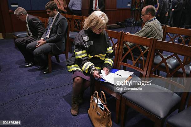 Wearing a firefighter's bunker coat given to her by 9/11 responders, Rep. Carolyn Maloney prepares for a news conference after the Zadroga 9/11...