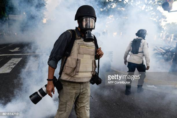 Wearing a flak jacket protective helmet and gas mask a photojournalist wades through a cloud of tear gas as opposition activists demonstrating...