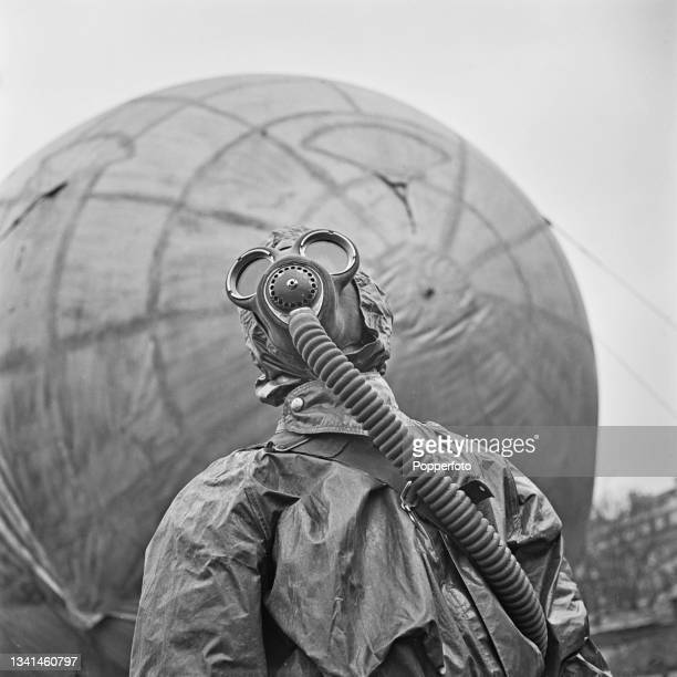 Wearing a gas mask respirator and full protective clothing, a member of a barrage balloon unit from RAF Balloon Command stands in front of a barrage...