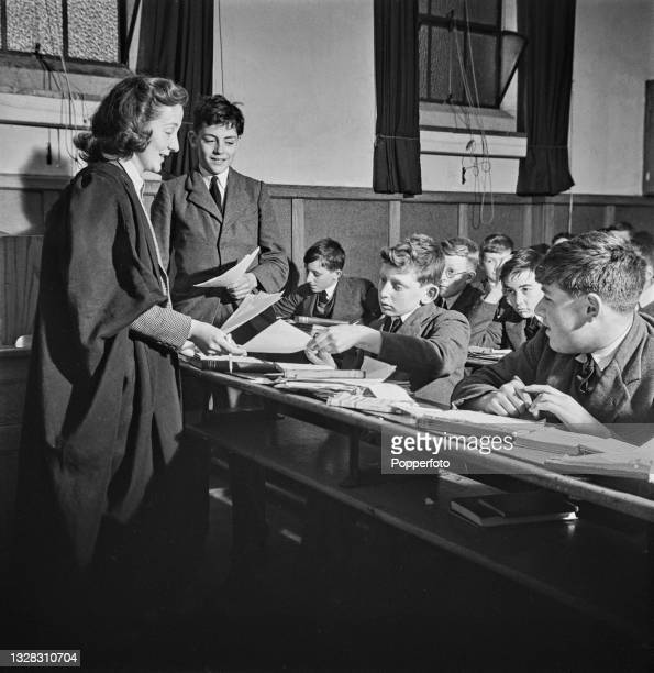 Wearing a gown, a female schoolmistress teaches a class of junior boys seated in rows of desks in a class at a public school in an English town...