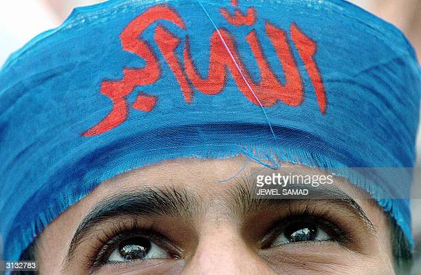 Wearing a headband reading AllahhuAkbar a Pakistani boy listens to Mutahida MajliseAmal leader Qazi Hussain Ahmed during an antiUS demonstration in...