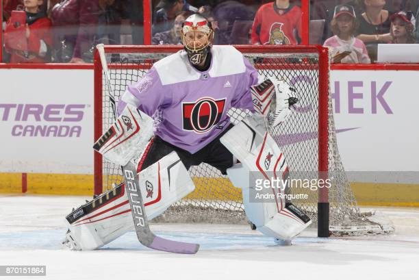 Wearing a lavender jersey for Hockey Fights Cancer night Craig Anderson of the Ottawa Senators warms up prior to a game against the Vegas Golden...