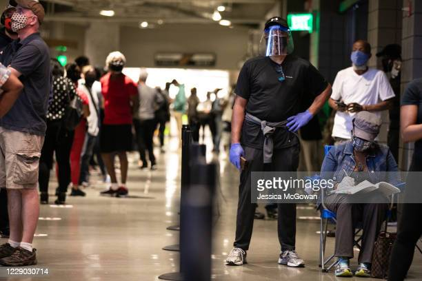 Wearing a mask and face shield, Wrick and Vera Cater wait in line at State Farm Arena to cast her ballot during the first day of early voting in the...