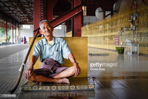 Wearing a paso, the men's version of the longyi, a sarong-style skirt worn by most Burmese, a local worshipper sits in quiet contemplation at the...