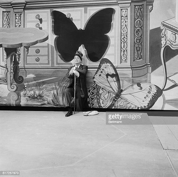 Wearing a peasant hat common to his native region in Spain madcap surrealist artist Salvador Dali stands triumphantly in front of one of the...