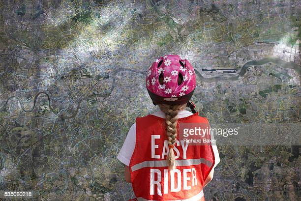 Wearing a pink-flowered safety helmet and a red reflective safety bib saying 'Easy Rider', a pig-tailed nine year-old girl cyclist examines a map of...