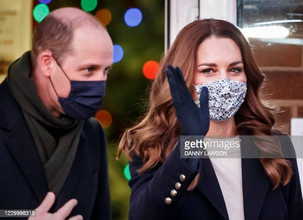 Wearing a protective face covering to combat the spread of the coronavirus, Britain's Catherine, Duchess of Cambridge , waves as she leaves after...