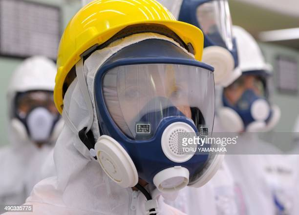 Wearing a protective suit and a mask US Ambassador to Japan Caroline Kennedy looks around at the central control room for the unit one and unit two...