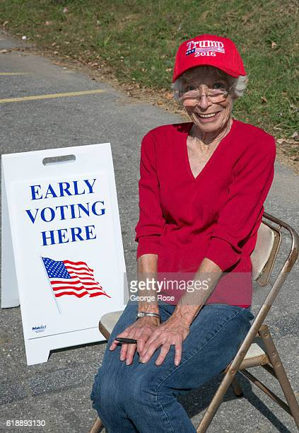 Wearing a red Donald Trump 2016 hat Lillian Tolley a 79yearold resident monitors an early polling location from across the street on October 21 2016...
