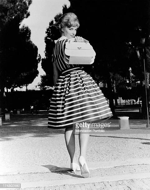 Wearing a refined striped dress Italian announcer and presenter Aba Cercato playfully displaying a white bag June 1960