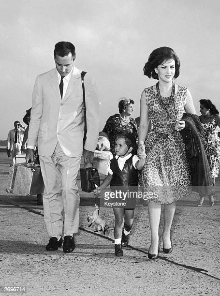 Wearing a sleeveless leopardprint dress and a triple strand of long beads film star Gina Lollobrigida She is at Rome airport with her husband Milko...