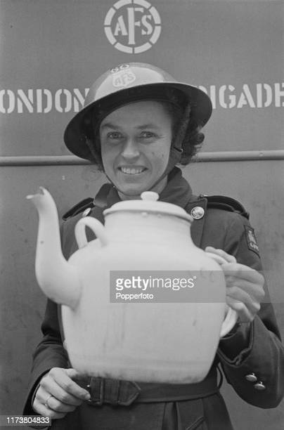 Wearing a steel helmet Enid Simpson of the London Auxiliary Fire Service holds up a large teapot used for brewing tea for staff on duty at a fire...